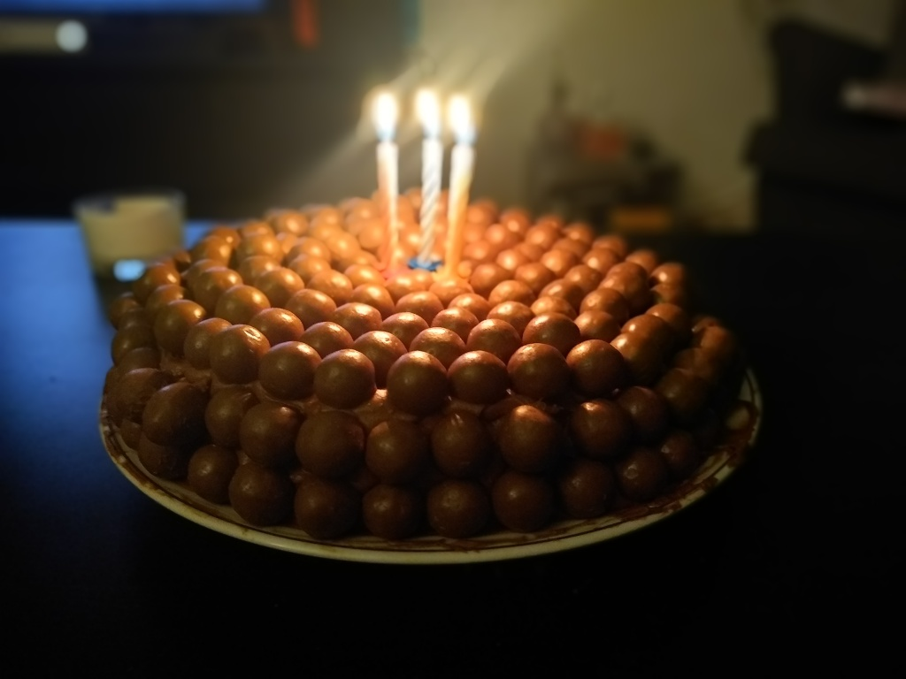 chocolate birthday cake, covered in round chocolate Malteasers with three lit candles on top.