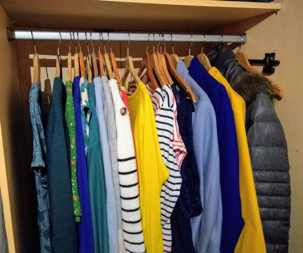 Colourful clothes hanging in a wardrobe.