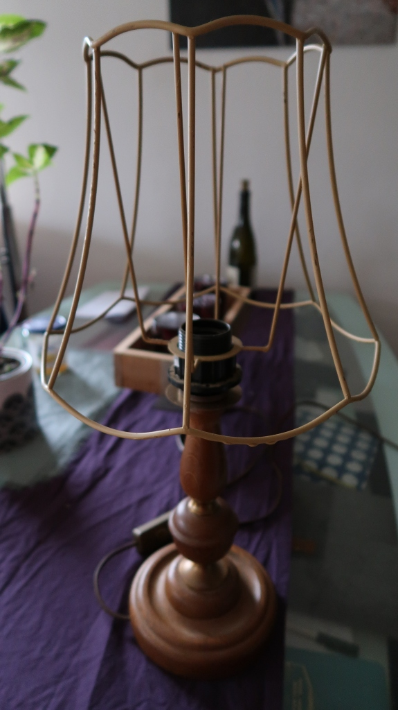 a wooden lamp stand with brown lampshade frame.