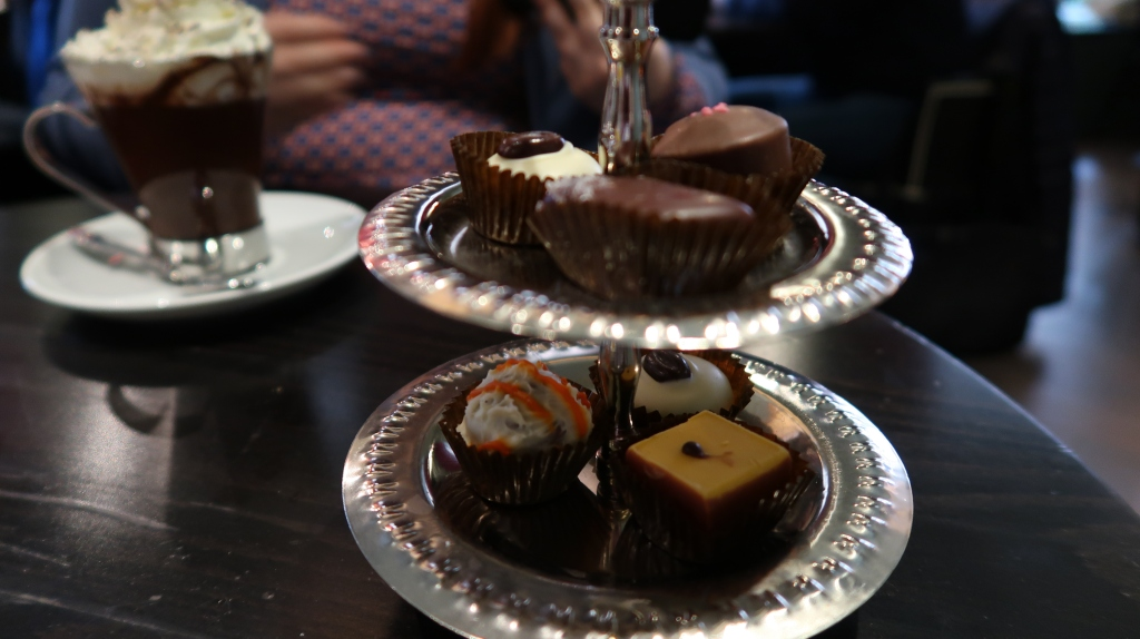 A hot chocolate in the background. In the foreground a two-tiered selection of six, hand-made chocolates.