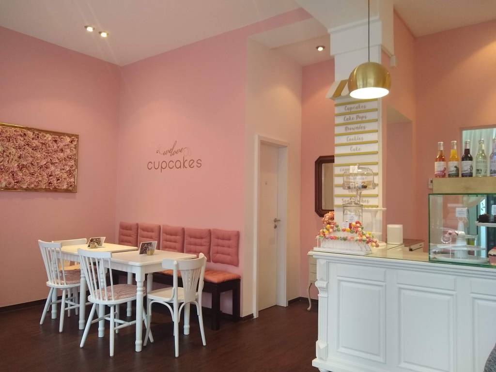 Cafe with pink walls, and white furniture. Decal with 'We Love cupcakes' written on the wall.