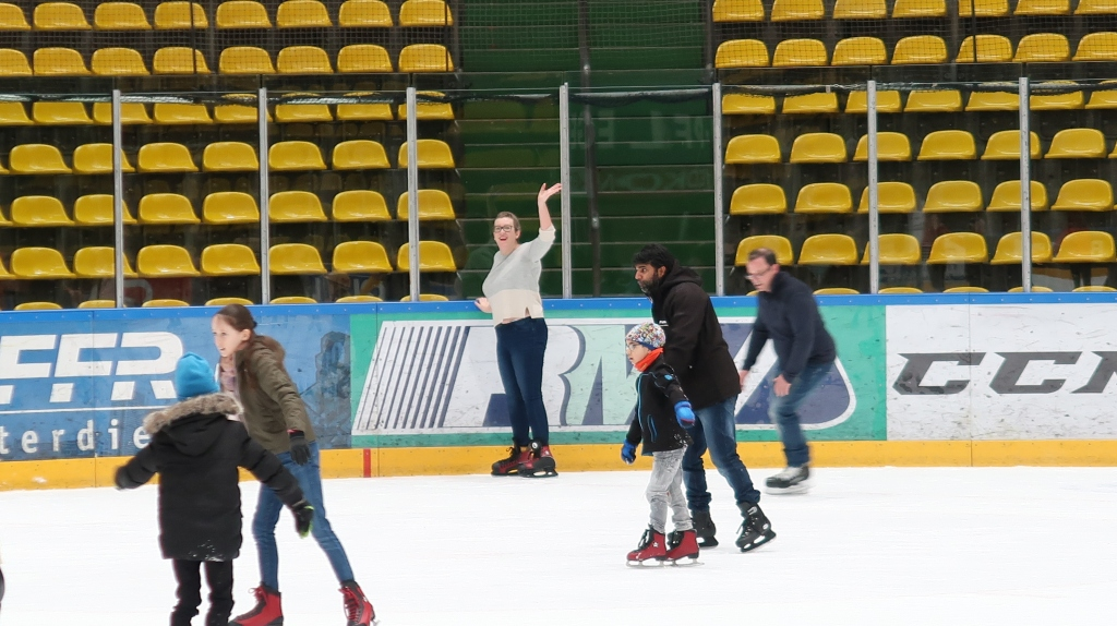 Woman on an ice rink, holding on to the  side and waving.