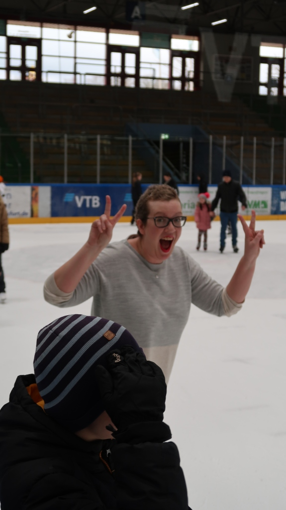 Woman on ice rink, smiling and giving the peace signs.