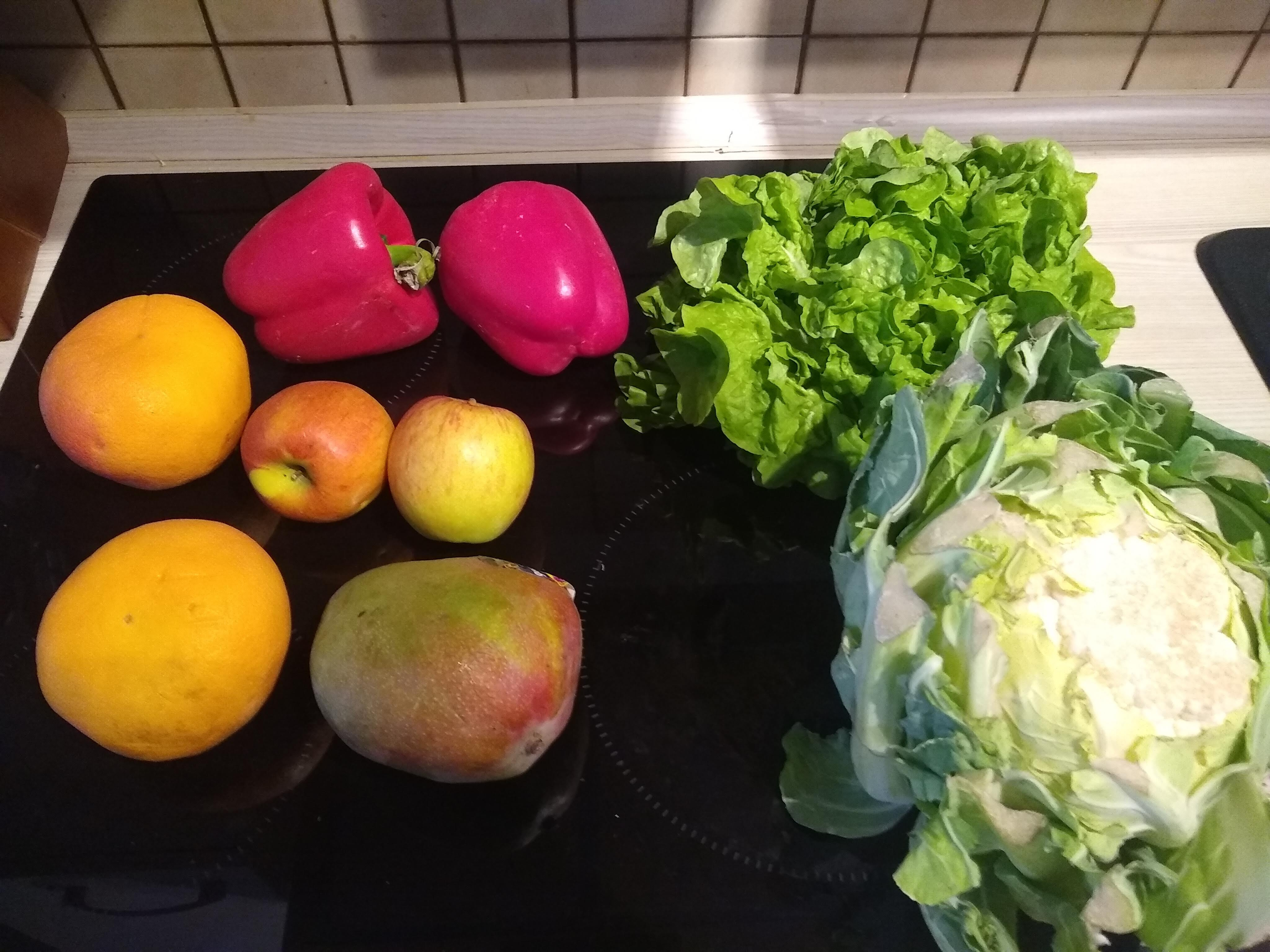 Two oranges, two apples, two red peppers, a lettuce, and a head of a cauliflower laid out on a cooker top.