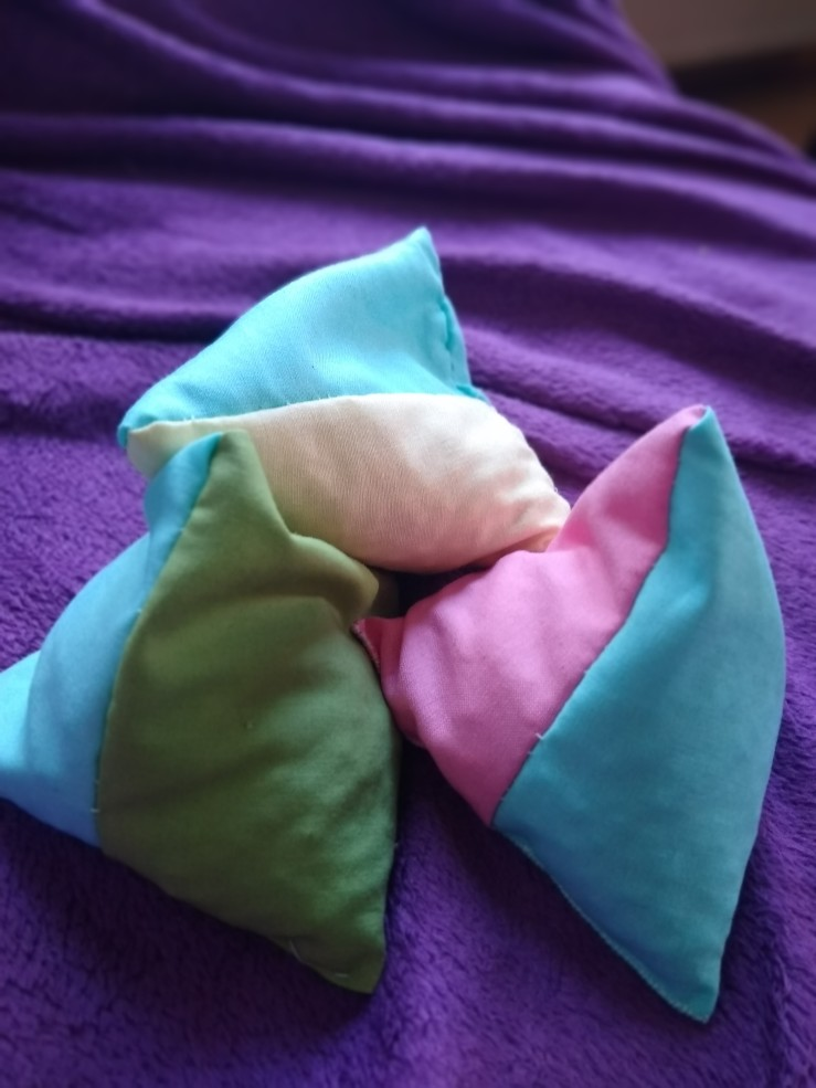 Three colourful juggling bean bags, filled with white beans.