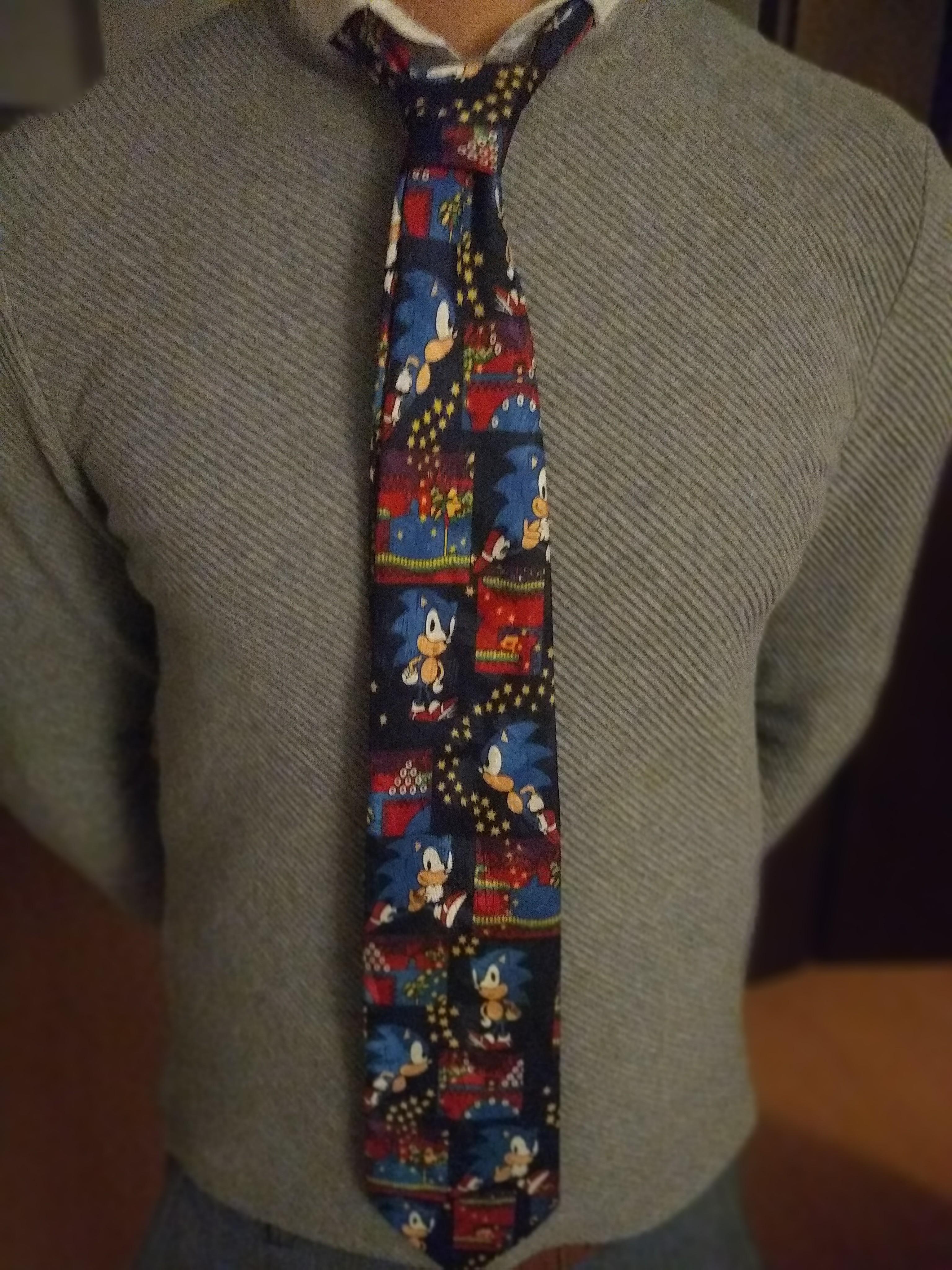 A man in a grey jumper, wearing a Sonic tie.
