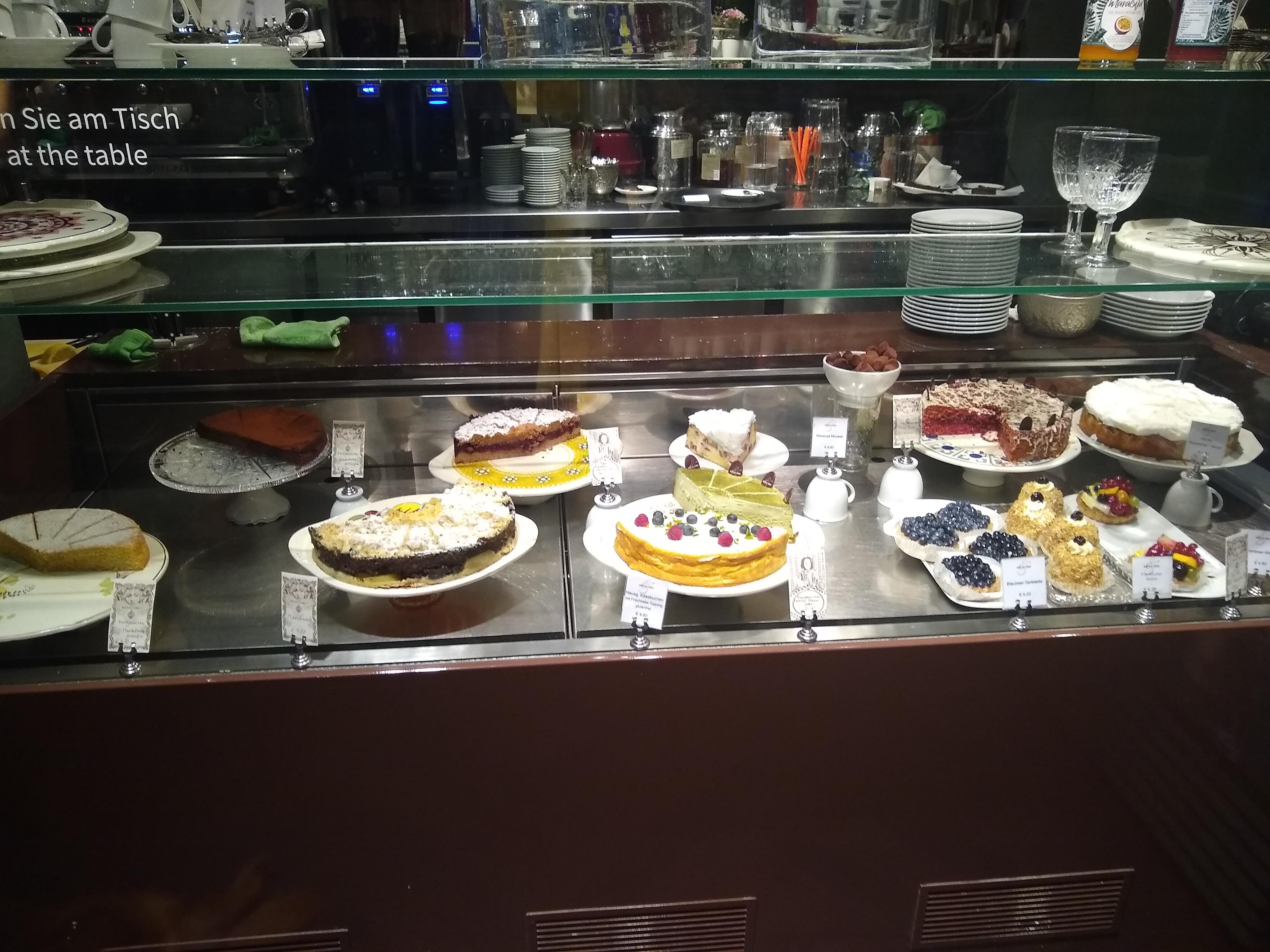 A counter filled with many different types of cakes.