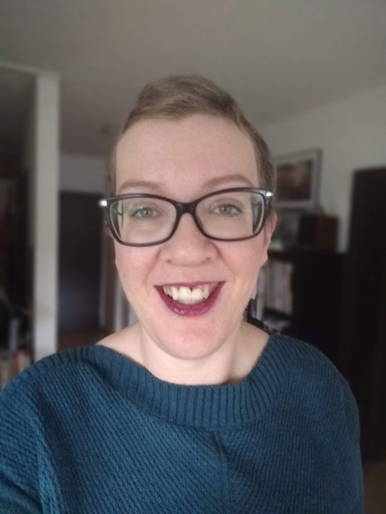Hannah in a green jumper, smiling with the purple lipstick on.