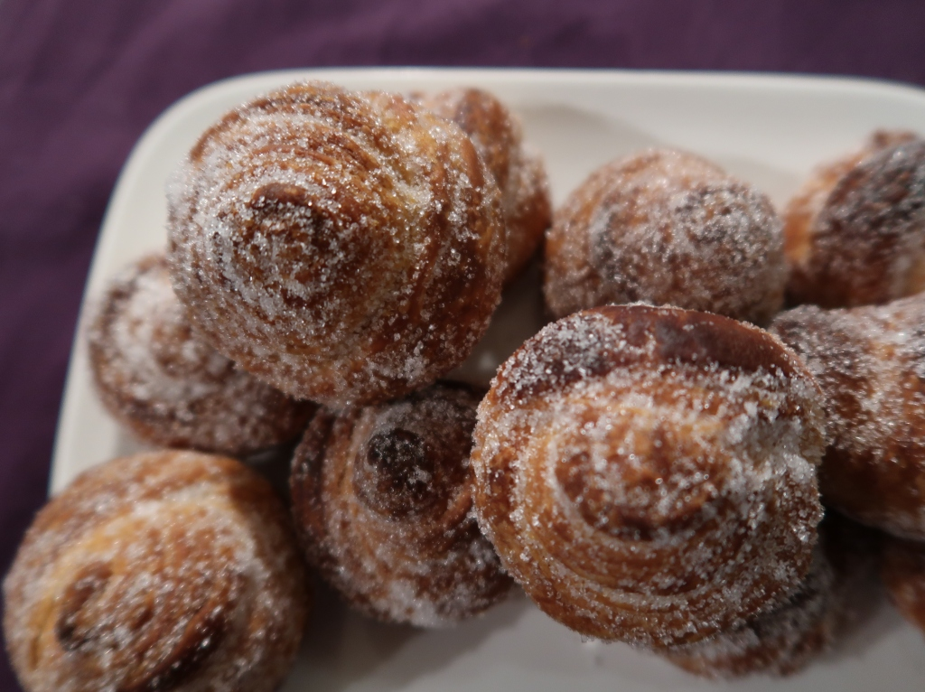 A top down view of a plate with sugary cruffins on top – pastry swirled like a rose.