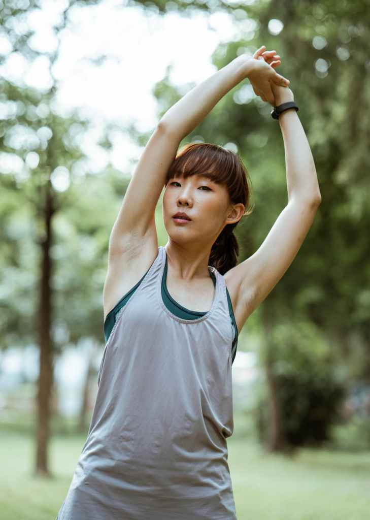 A person in sportswear, in a forest. They are stretching their arms over their head as if in a yoga pose.